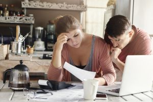 Young married couple facing financial problem during economic crisis. Frustrated woman and unhappy man studying utility bill in kitchen, shocked with amount to be paid for gas and electricity